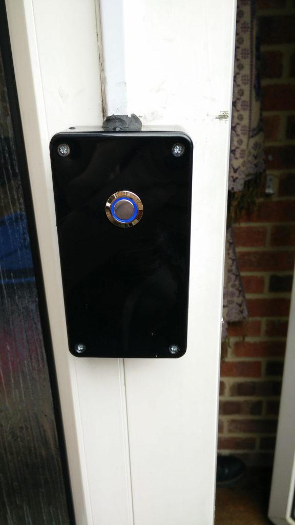 Doorbell with blue LED ring mounted in enclosure
