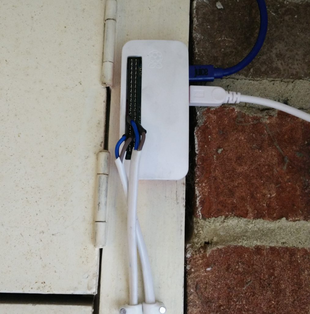 Rasberry Pi Zero mounted on wall with USB cables and GPIO connectors
